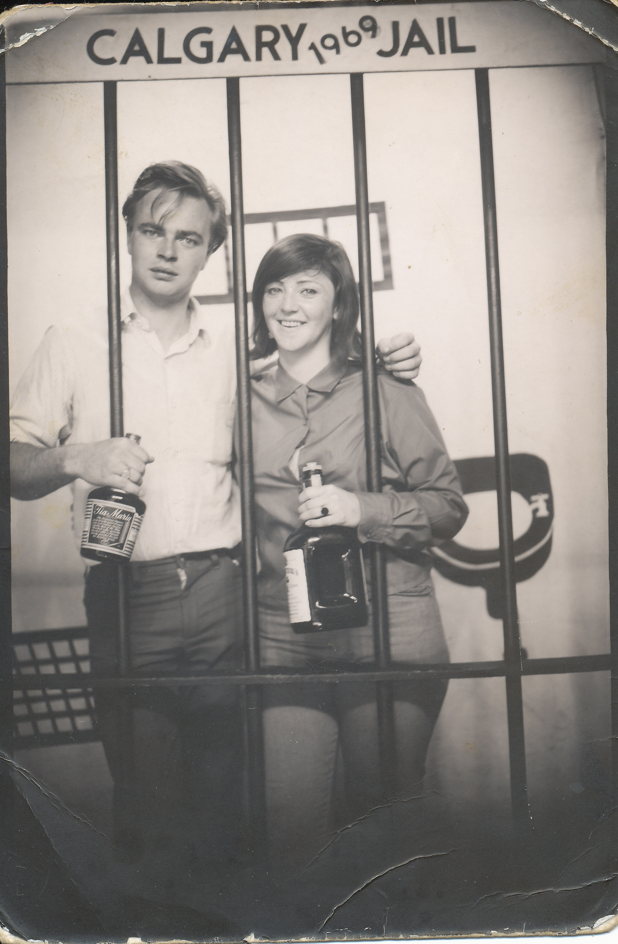 young man and women both holding liquor bottles and behind mock prison cell bars