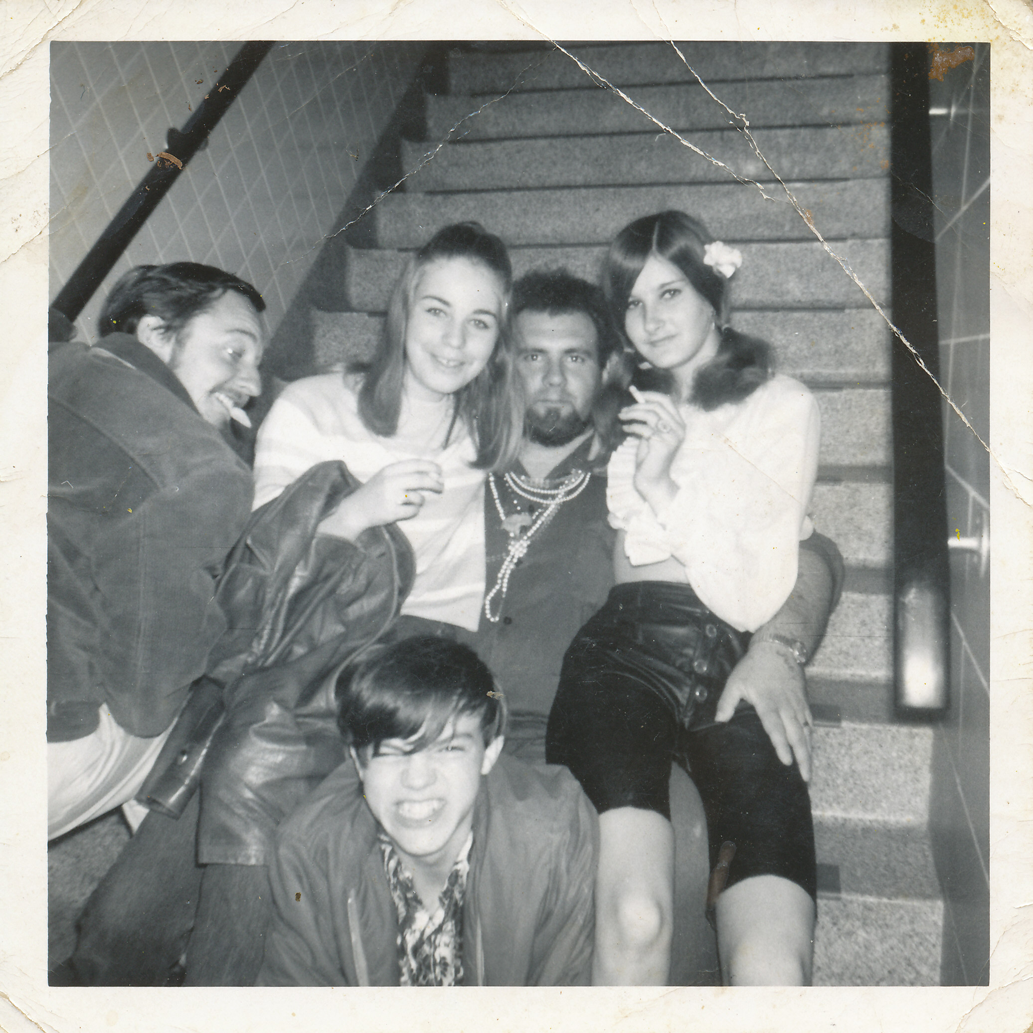 2 young girls, one young boy and 2 older young men sitting on stairs