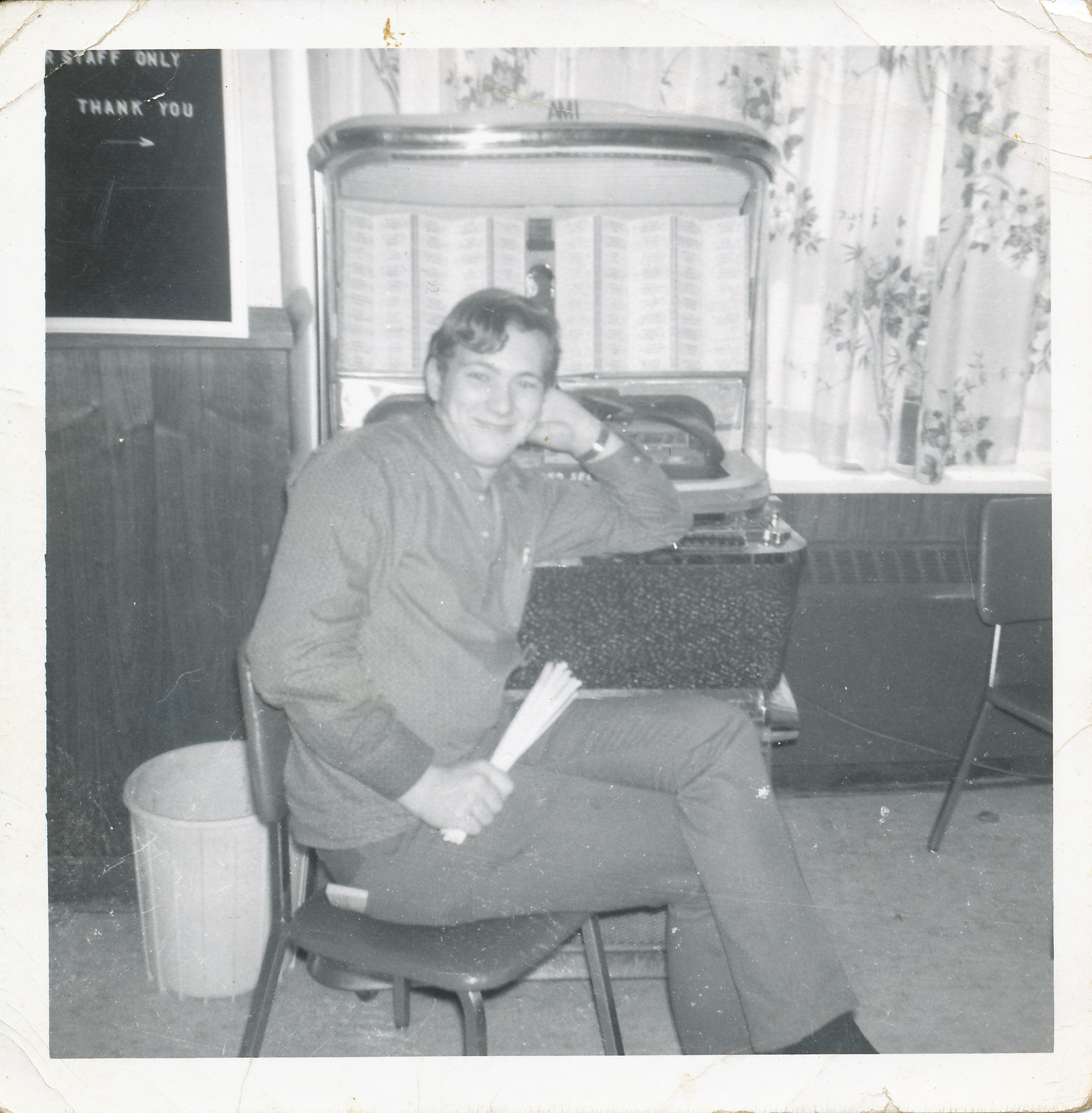 young man sitting on chair in front of a jukebox