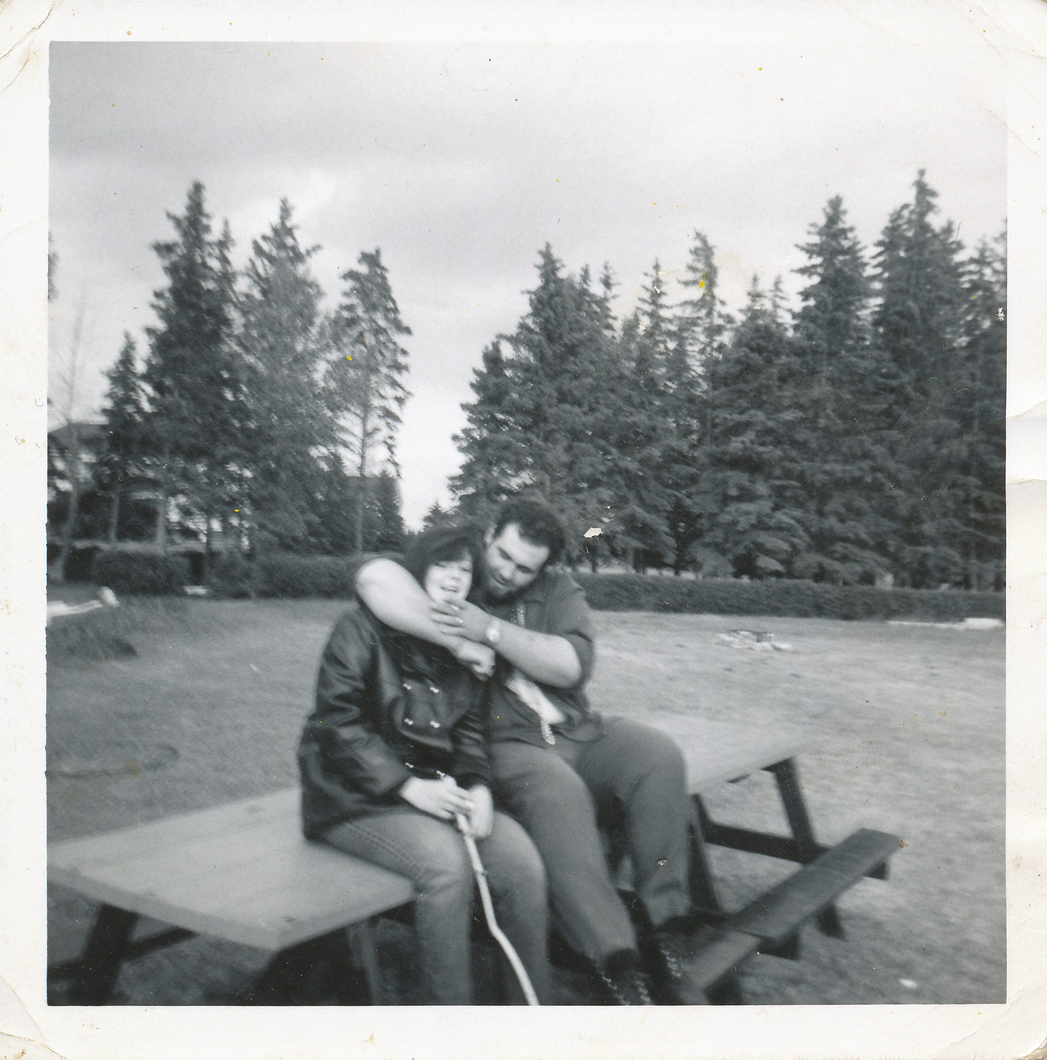 young woman and man sitting on picnic bench on playing field