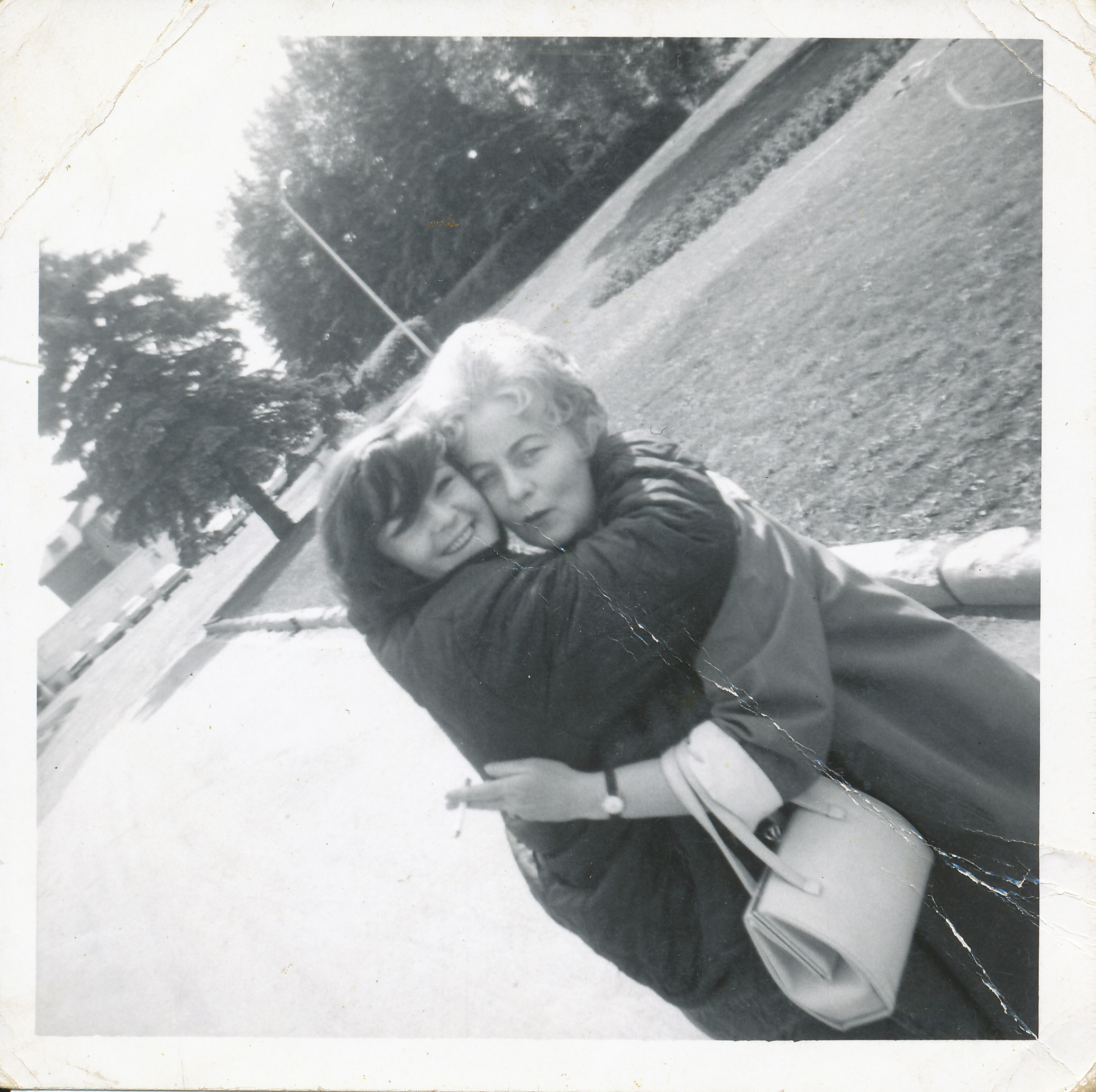 young woman and old woman hugging, 1960s style clothing