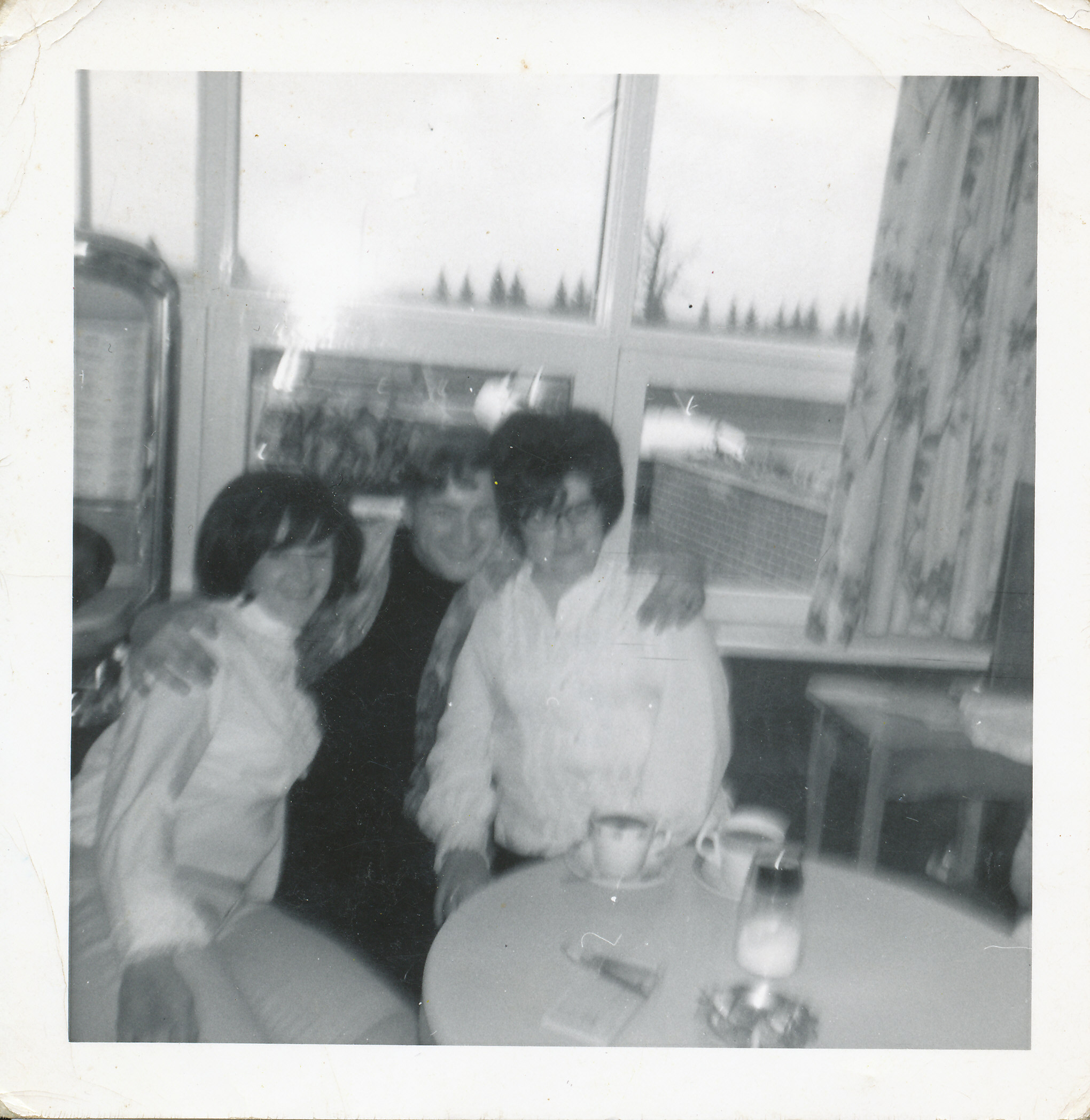 3 young people sitting at cafeteria table with coffee cups