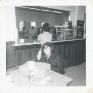 young woman sitting at table in cafeteria with serving counter behind