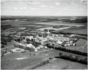 black and white aerial of large institution with old buildings surrounded by prairie fields