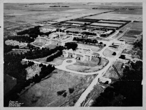 aerial photography of large asylum complex showing old brick main building, roads, outbuilding and farming area