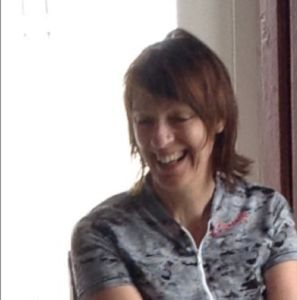 Head and shoulders shot of smiling apparent woman with dark hair, wearing cycling shirt.