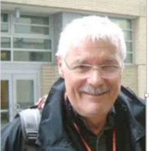 Head and shoulders shot of apparent man with white hair, mustache and glasses smiling.