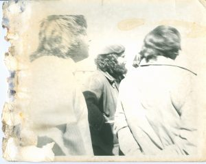 three men standing with their backs to the camera