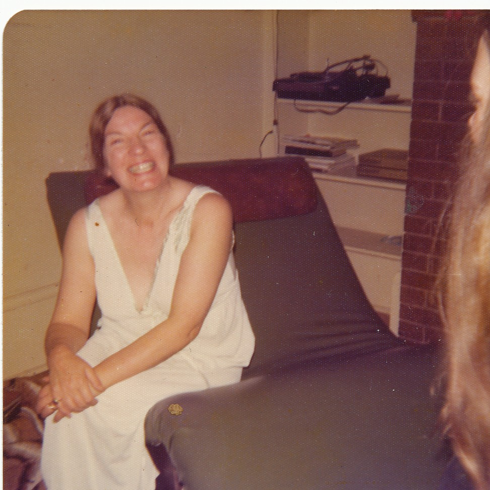 smiling woman wearing nightie sitting on couch
