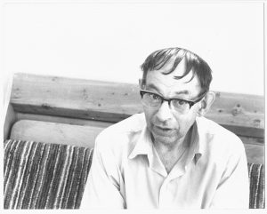 man with dark hair and glasses sitting on couch
