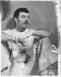 man with dark hair and mustache sitting with his knees up