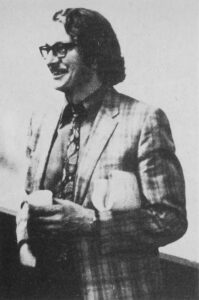 1970s man with glasses, sports jacket and tie, holding cup of coffee