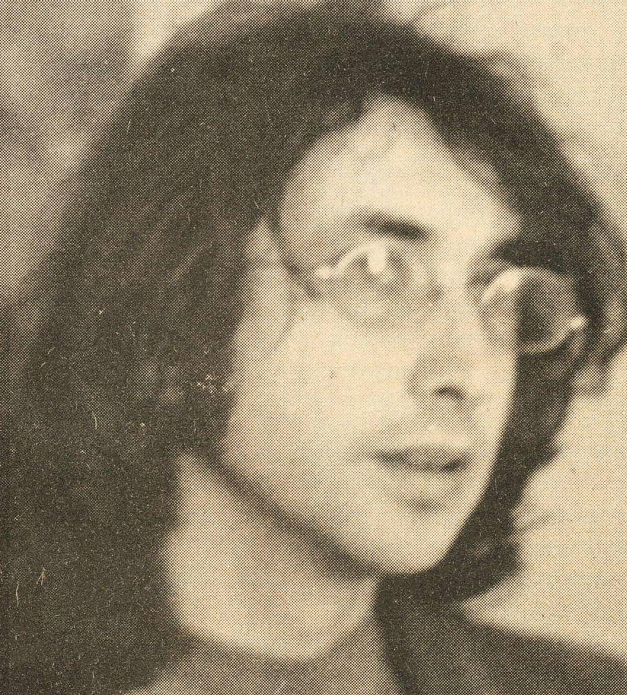 young man with long dark hair and glasses, 1970s style