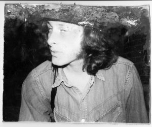 man with long hair and a hat