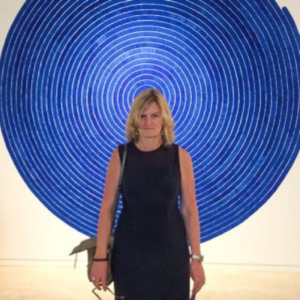Body shot of blond serious looking apparent woman standing against blue circular wall art.