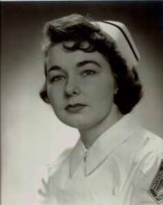 1950s graduation photo of young woman wearing white cap and nurses costume with dark hair