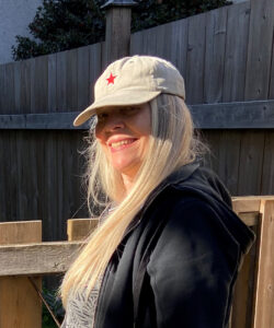 woman in baseball cap with big smile and long blond/white hair
