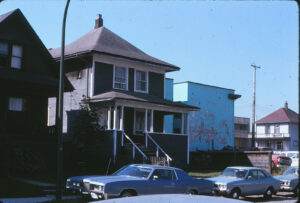 old house with cars parked in front