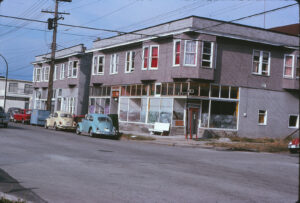 older corner store front with cars parked in front
