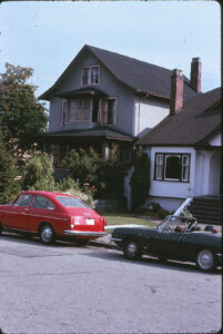 old house and front garden with cars parked in front
