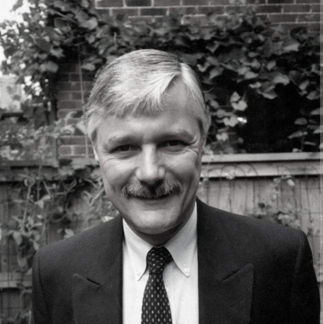 smiling white man with mustache wearing jacket, dress shirt and tie in garden