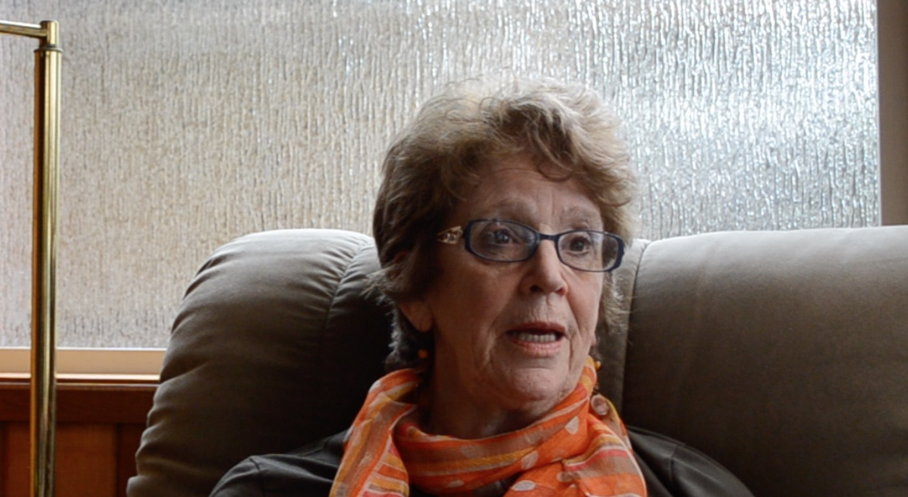 older woman with brown hair and glasses