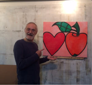 person holding painting of a red apple and a red heart