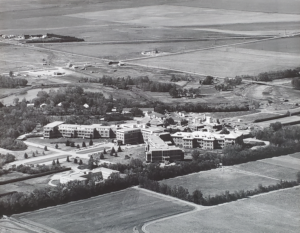 black and white aerial photograph of large complex institution set in prairie fields
