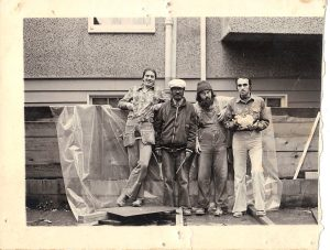 4 men standing in front of a building site wearing work clothes.