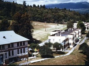 1930s and 1950s institutional buildings on wooded and grassy hillside, view of the ocean behind.