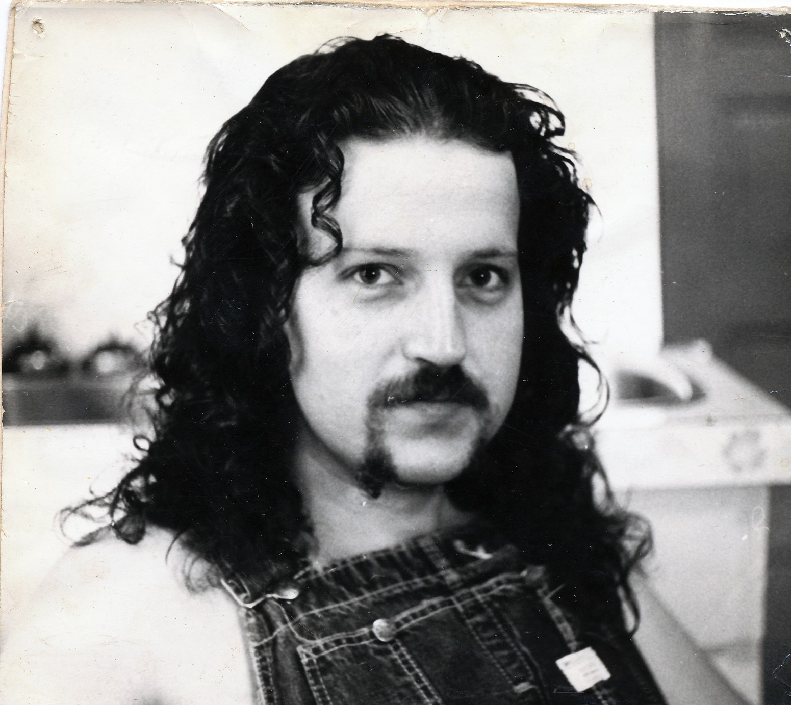 head and shoulders shot of man with thick curly dark hair and facial hair