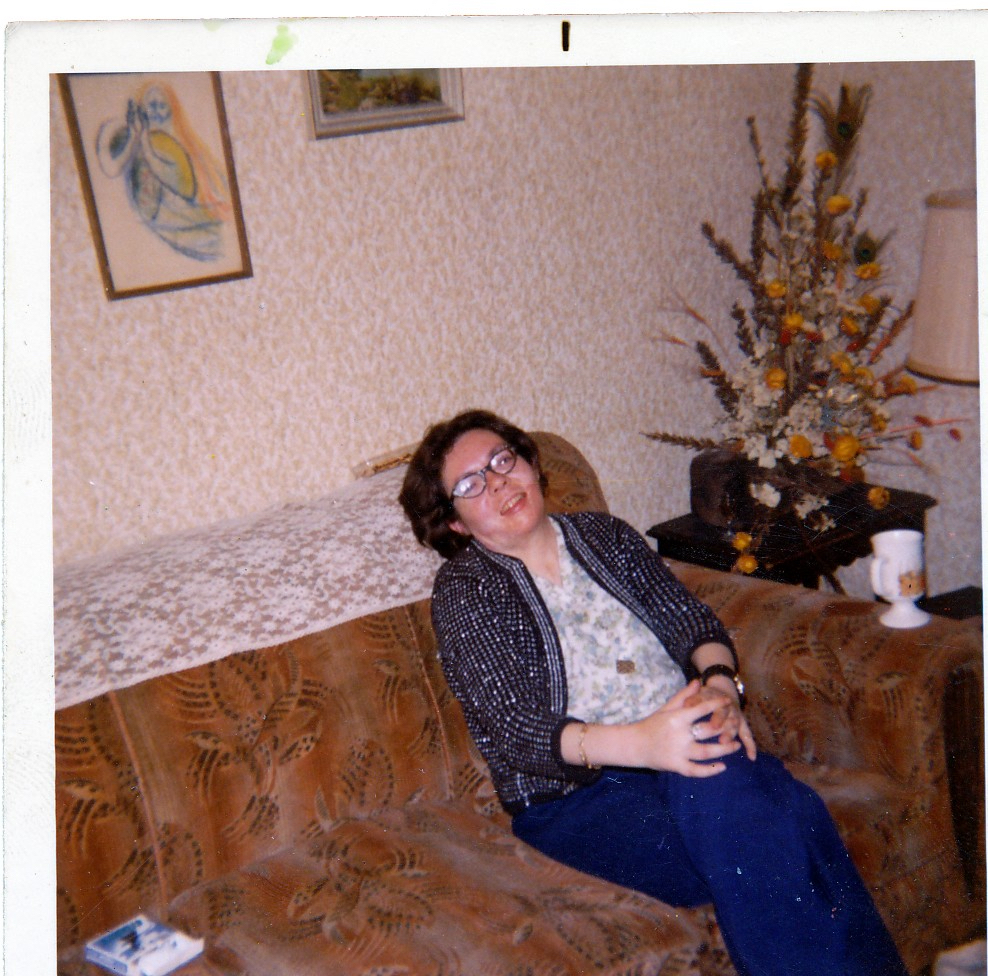 woman with glasses and dark hair sitting on couch