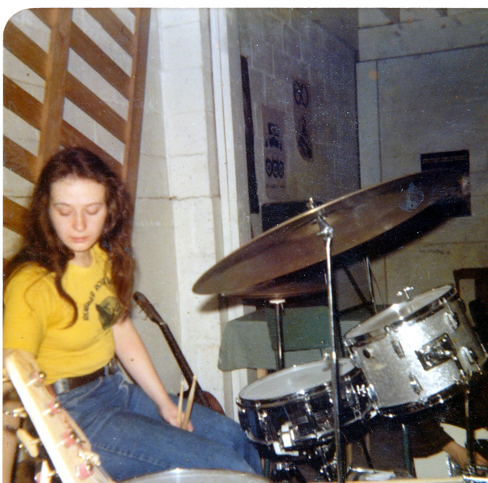woman with long dark hair sitting at drum kit