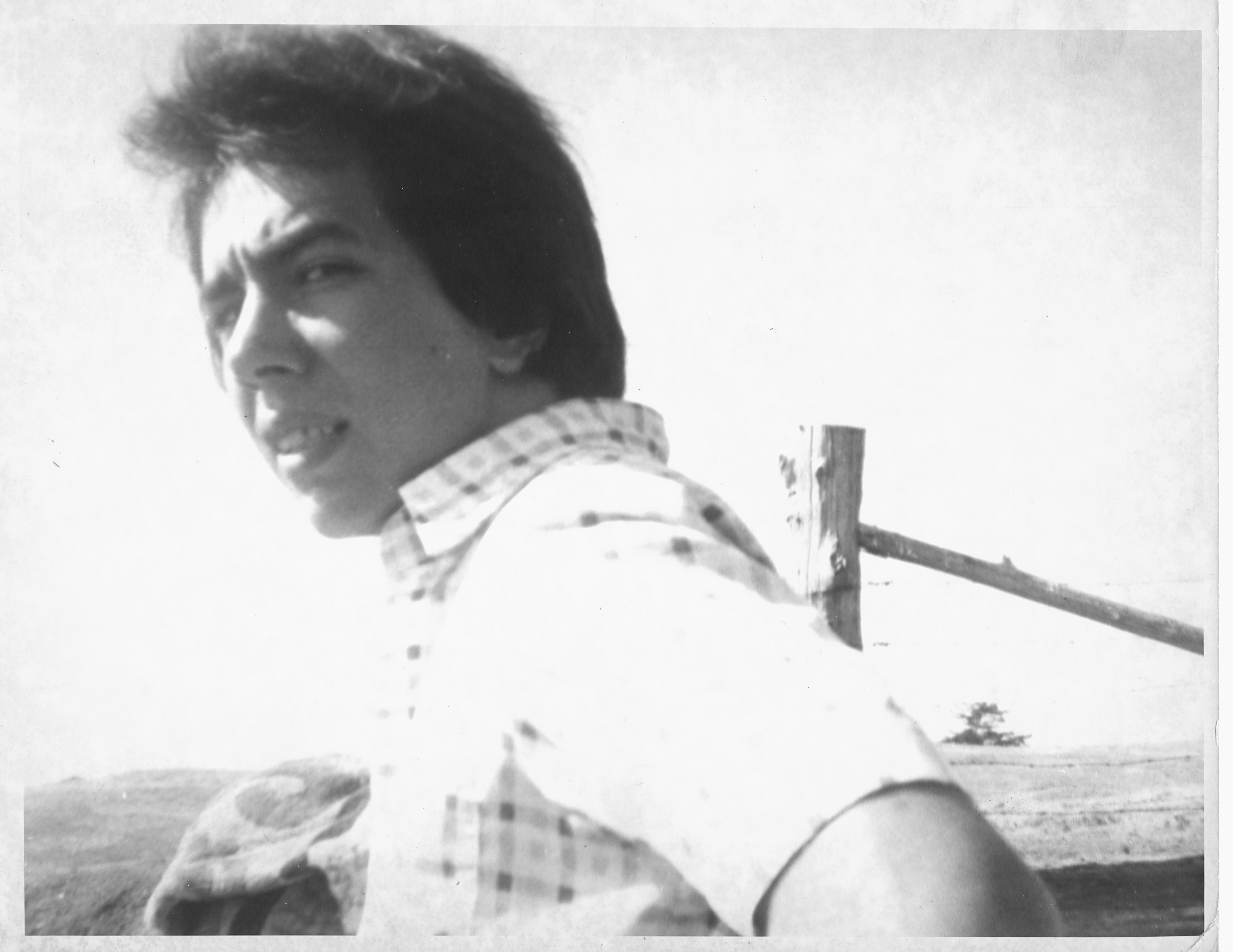 man with dark hair looking back over his shoulder at the camera