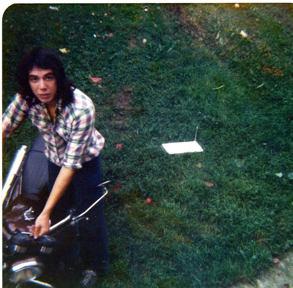 man with dark hair on moter bike