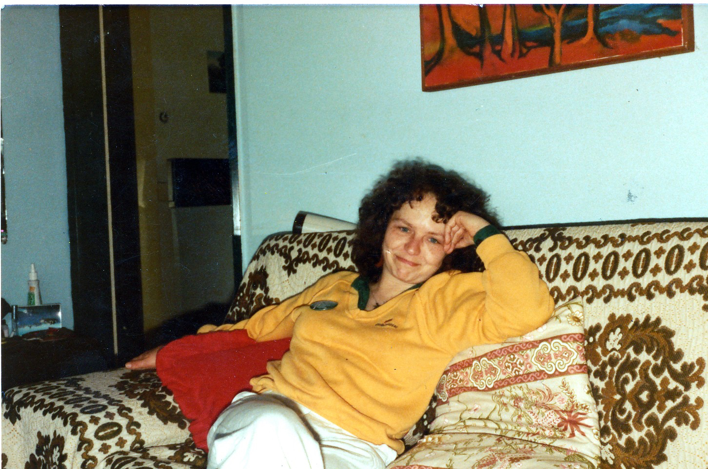 woman with curly hair sitting on couch