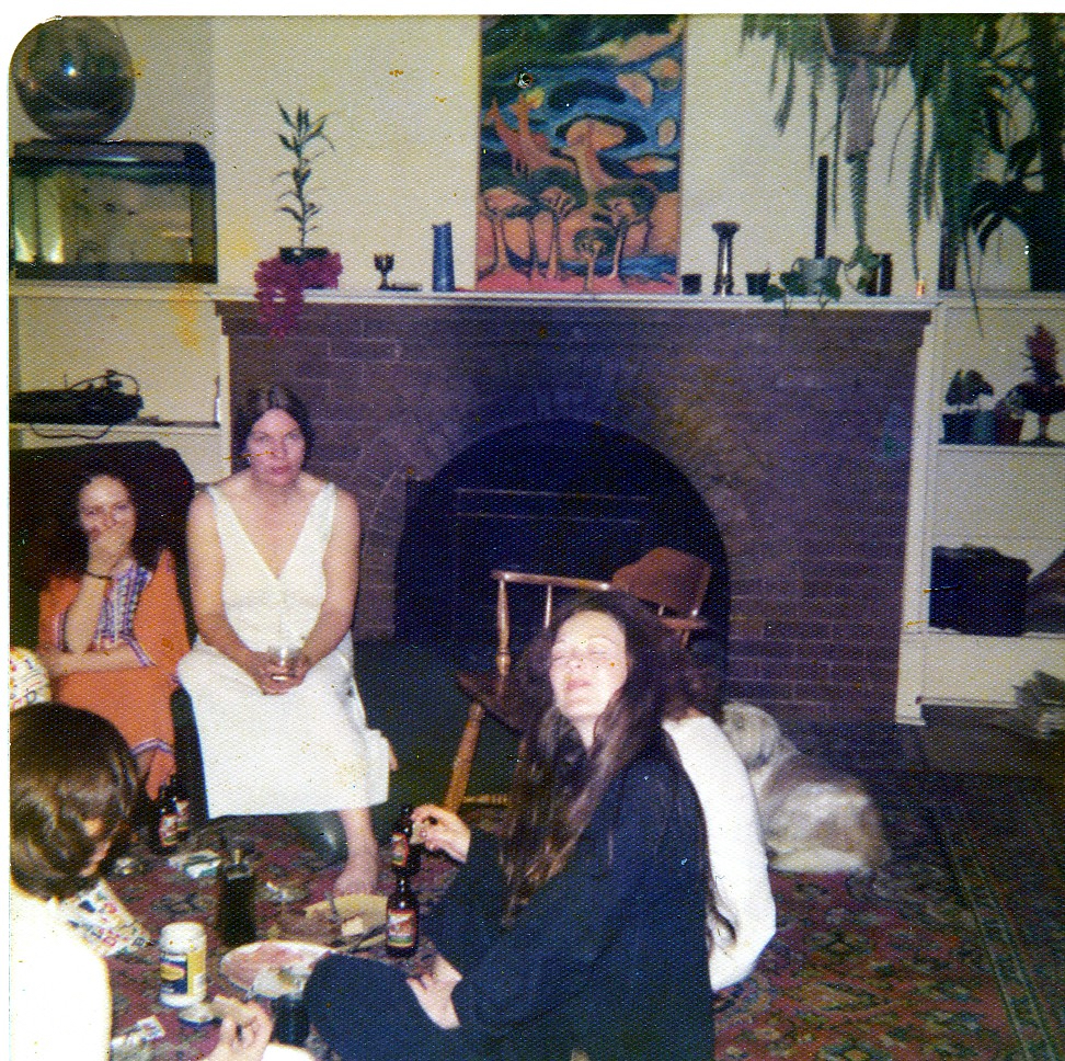 3 women sitting in living room in front of large fireplace