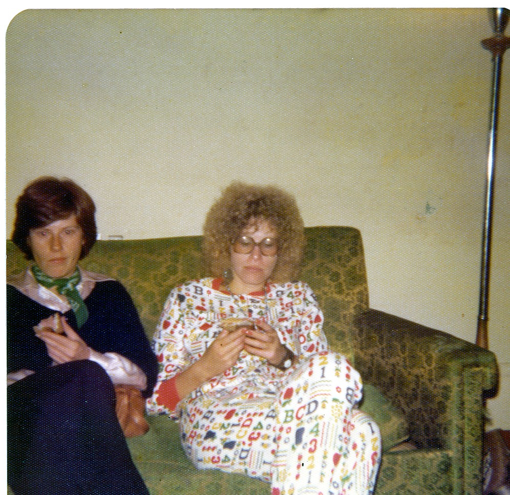 two women in night dresses sitting on a couch