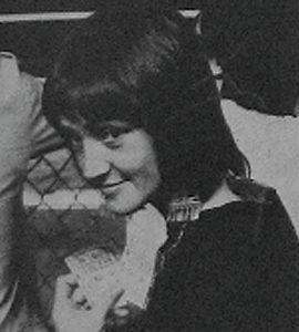 young woman with dark hair looking over her shoulder at the camera
