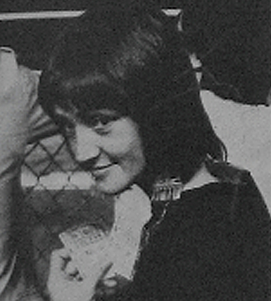 dark haired young woman looking over her shoulder at the camera with a slight smile