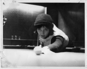 young woman in hat playing pool