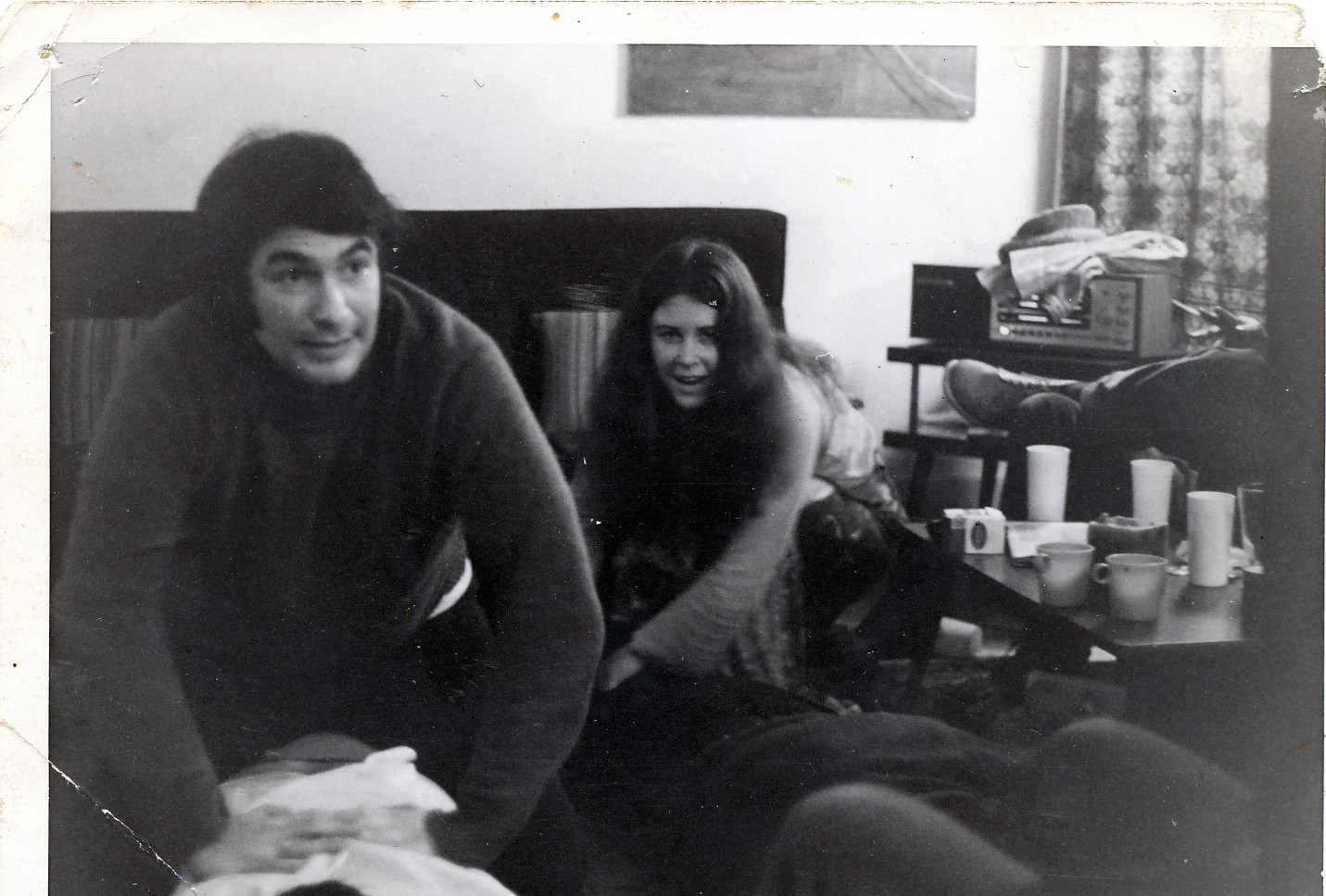 dark haired man and women seated in living room.