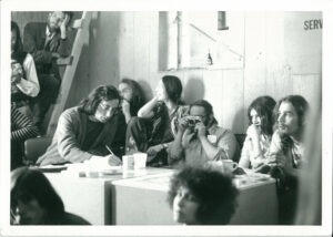 group of 1970s peole sitting around a table in a basement.  One has camera and another is writing something. Others laugh or talk.