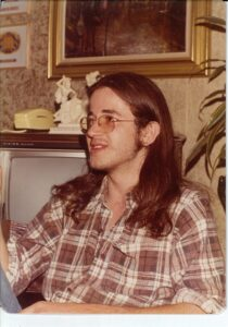 person with long brown hair sitting in front of TV wearing a plaid shirt