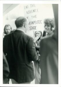 1970s protest scene, media person with headphones and mic talks to older person