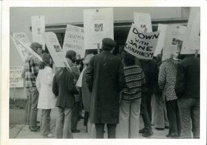 group of 1970s people protesting holding signs with slogans