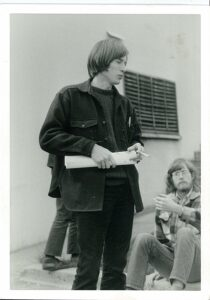 1970s person holding rolled up paper in hand. Another 1970s person sitting on the ground.