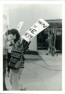 person wearing oversize patterned sweater and carrying protest sign.