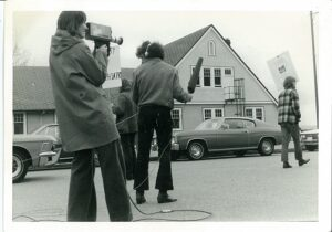 1970s media people with camera and mic, in background one protester with sign, 1970s cars and institutional building