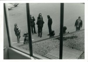 6 people viewed from a window above standing on sidewalk